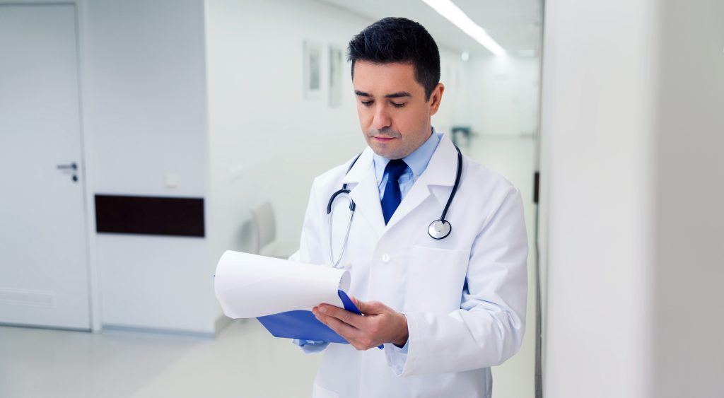 doctor writing to clipboard at hospital